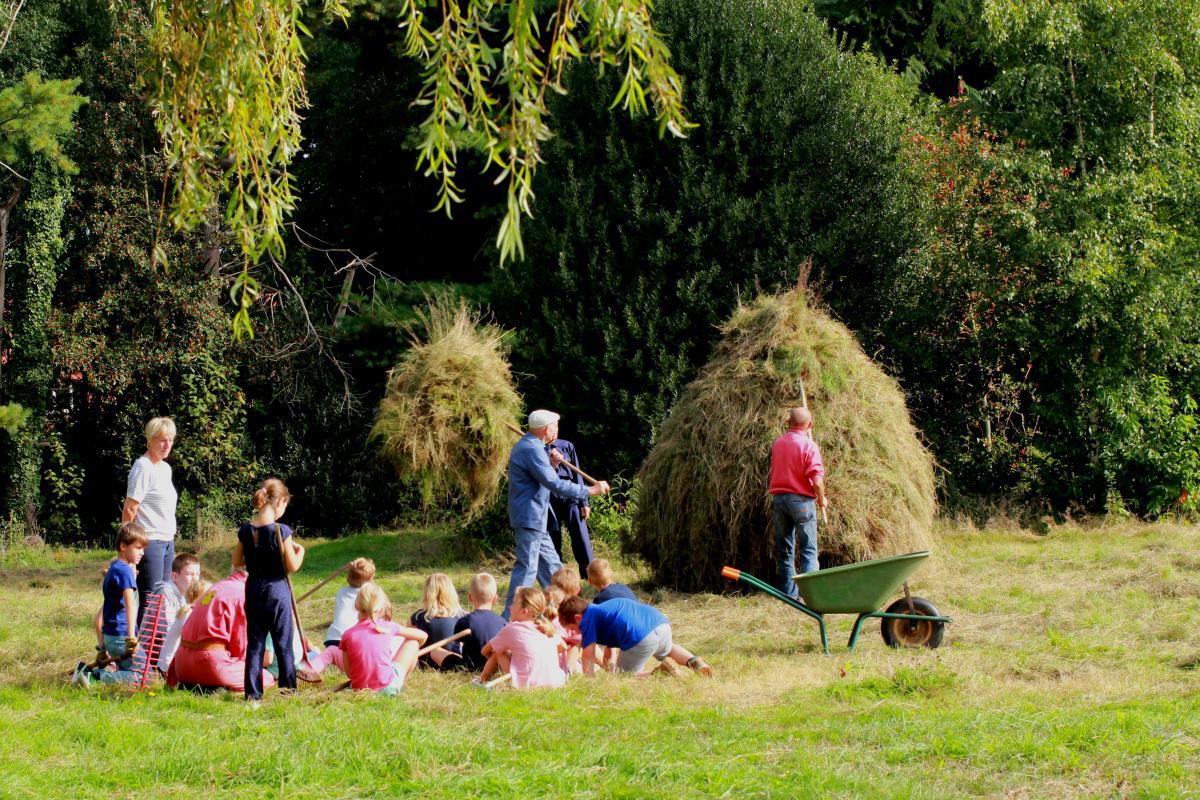 Kinderen zitten bij een grote hoop van hooi