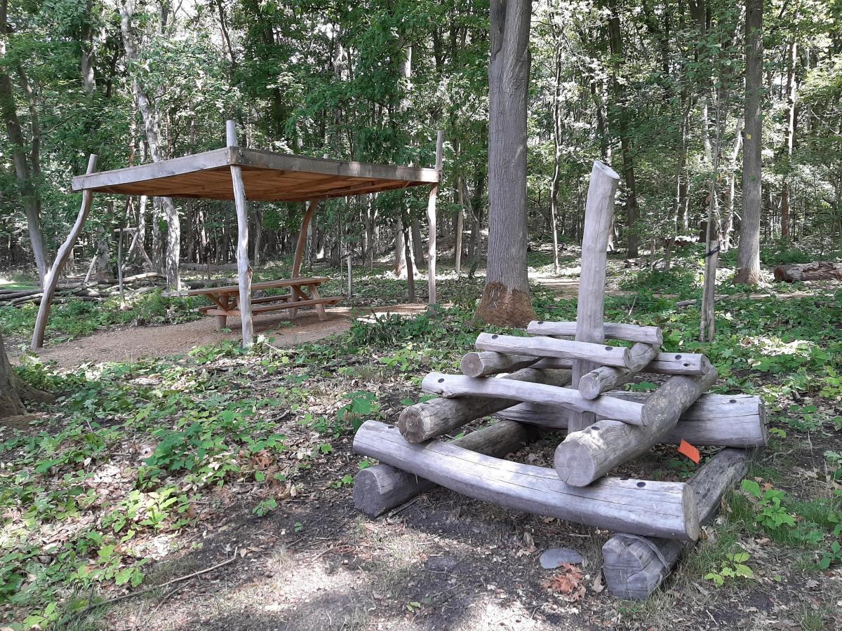 Een overdekte picknickbank en een kleine klimtoren in hout